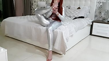 Woman in silver latex playing on the bed