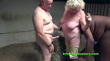 An older woman services black and white cocks