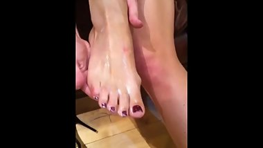 Rubbing lotion into red feet after clubbing in high heels