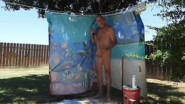 A daddy taking a shower, outdoors, on his patio.