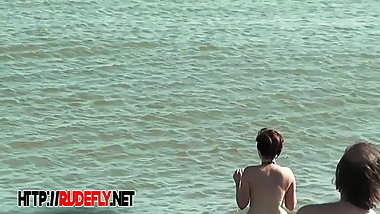 Plump breasted girl caught in a voyeur beach nudism video