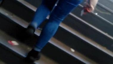 Young woman in tight blue pants who goes up the stairs