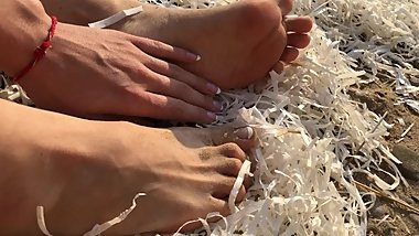 Cute sexy bare feet on sand near sea