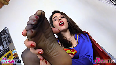Supergirl in black pantyhose shows off feet and sniffs them