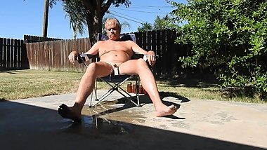 A naked daddy sunbathes and pees.