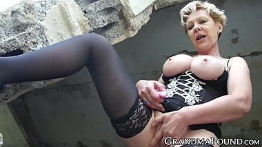 Kinky grandma fucks pussy with dildo in outdoor solo