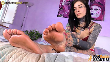 Tattoed redhead in lingerie gives herself a foot massage